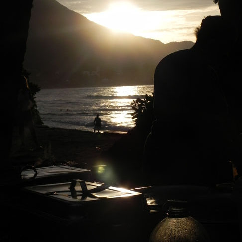 The sunset glints off a chaffing dish at the Wednesday market on Mahe's Beau Vallon beach